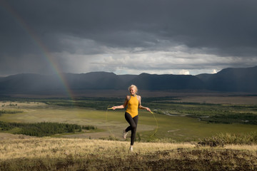 Young lesbian woman jumping with Jump rope in the natural area with mountains and rainbow on the background