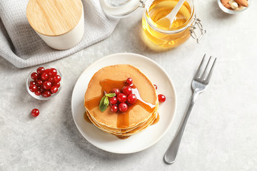 Stack of tasty pancakes with berries and syrup on table, top view