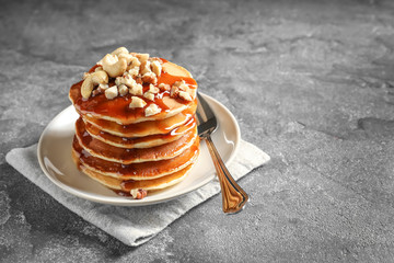 Stack of tasty pancakes with nuts and syrup on table