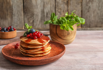 Stack of tasty pancakes with berries and syrup on table