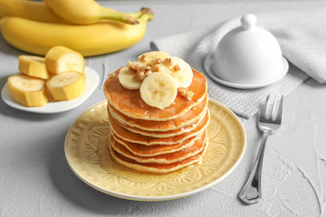 Stack of tasty pancakes with banana, nuts and honey on table