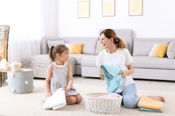 Housewife with daughter folding freshly washed towels in room