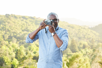 Portrait of African American Senior man with a vintage film camera laughing outdoors