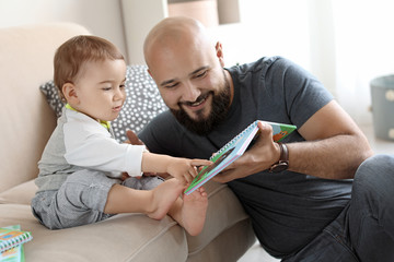 Dad reading book with his little son in living room
