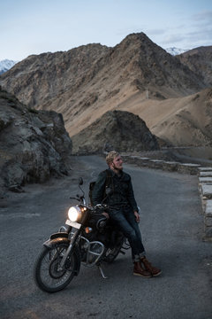 Young man sitting on the motorcycle with headlights on, surrounded by desert and mountains