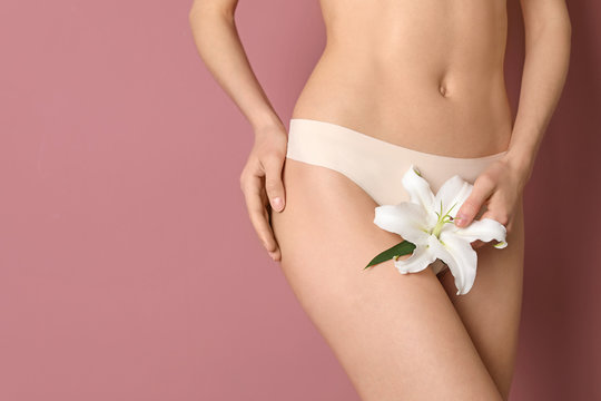 Young woman with flower showing smooth silky skin after epilation on color background