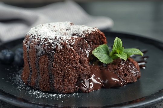 Delicious fresh fondant with hot chocolate and blueberries served on plate. Lava cake recipe