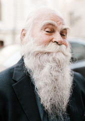 close up portrait of old man with white Gray-haired beard looking like Santa Claus