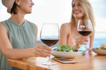 Young women with glasses of wine at table