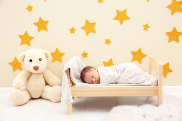 Adorable newborn baby sleeping in small bed