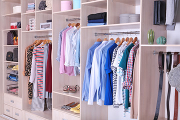 Large wardrobe with different clothes and shoes