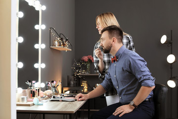 Professional makeup artist working with client in dressing room