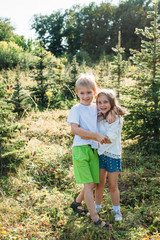 Lovely children couple posing at camera outdoors