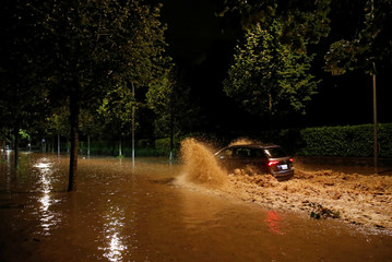 A car drives through water on the Quai d'Ouchy after a flash flooding during a heavy rain fall in Lausanne