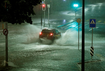 A car drives through water on the Avenue de Mon-Repos after a flash flooding during a heavy rain fall in Lausanne