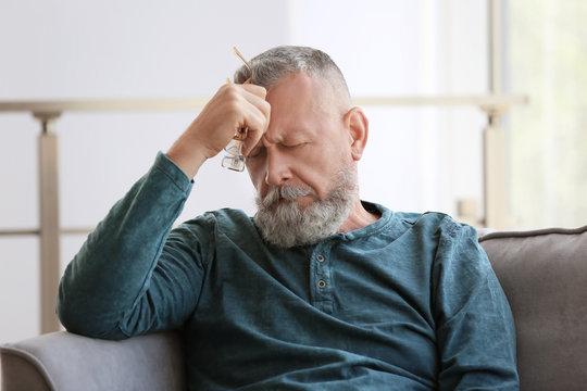 Depressed senior man sitting in armchair indoors
