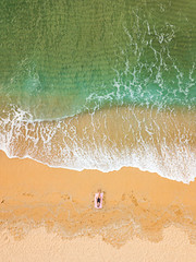Woman sunbathing alone on an empty beach