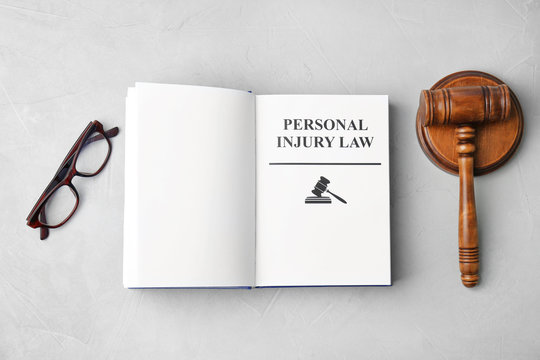 Book with words PERSONAL INJURY LAW, gavel and glasses on grey background, top view