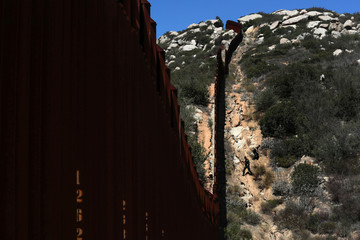 Border patrol agents search for illegal immigrants along the wall on the U.S. border with Mexico in California