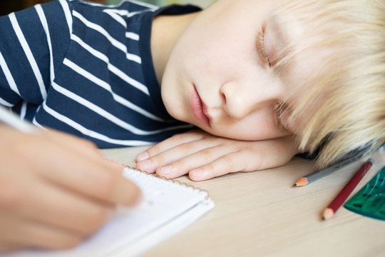 Boy sleeping on the desk while doing his homework in notebook. Close up.