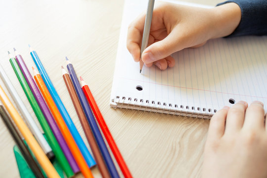 Kid holding pencil and writing in notebook. Colorful pencils on the desk. Close up.
