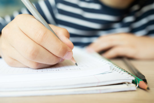 Kid holding pencil and writing in notebook. Close up.