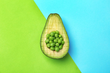 Composition with ripe avocado and green peas on color background, top view