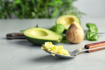 Spoon with tasty avocado pulp on table