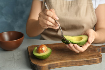 Woman scooping ripe avocado with spoon at table