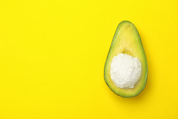 Composition with ripe avocado and ice cream on color background, top view