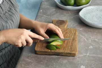 Woman cutting ripe avocado on wooden board at table