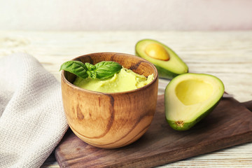 Bowl with guacamole and ripe avocado on table