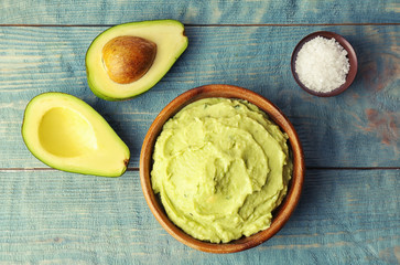 Flat lay composition with guacamole sauce, salt and ripe avocado on wooden background
