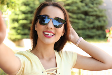 Young woman taking selfie outdoors on sunny day
