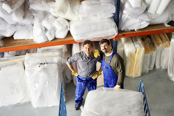 Happy Workers Standing By Mattresses In Warehouse At Sofa Worksh