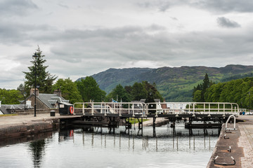 Fort Augustus, Scotland - June 11, 2012: Lock with water flowing over closed dark brown doors on Oich River Canal showing green grass and white houses on both sides under heavy gray sky. Hills