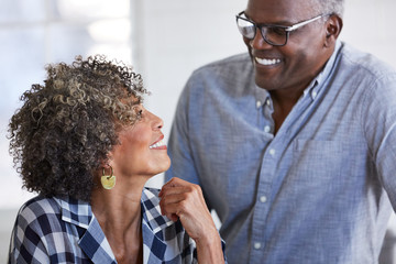 Senior African American couple at home smiling at each other