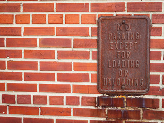 Rusted No Parking Sign on a Red Brick Wall