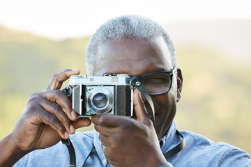 Close up portrait of African American Senior man taking a photo with a vintage film camera outdoors