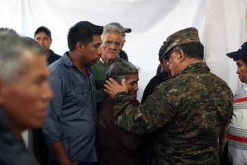 A Guatemalan army officer comforts the mother of Aura Yolanda Perez Paz, 17, who died during the eruption of the Fuego volcano, in Alotenango