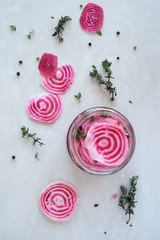 Overhead of candy striped beetroot sliced in pickling brine
