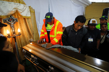A municipality policeman helps to dry the coffin of Aura Yolanda Perez Paz, 17 who died during the eruption of the Fuego volcano, in Alotenango