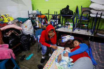 An evacuated family is pictured in a provisional shelter in a local school after the eruption of the Fuego volcano damaged their community in Alotenango