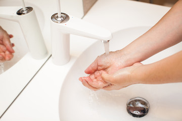 close up photo of woman washes her hands with soap and water
