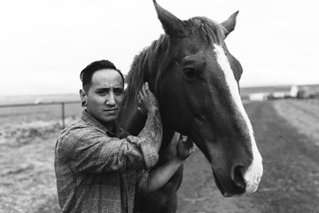Man Looking at Camera and Standing with Horse