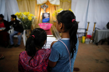 Sisters of Aura Yolanda Perez Paz, 17, who died during the eruption of the Fuego volcano, stand by her coffin, in Alotenango