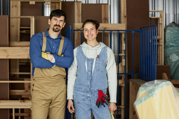 Confident Workers Against Incomplete Furniture At Sofa Workshop