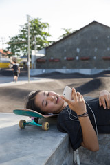 Young Japanese girls listening music in a skate park