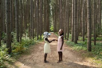 Two black girls wearing masks shaking hands