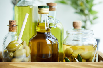 glass with spoon and green olives, jar, various bottles of aromatic olive oil with and branches on wooden tray